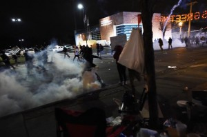 Demonstrators flee as police fire tear gas during a demonstration to protest the death 18-year-old Michael Brown in Ferguson, Missouri, on November 24,