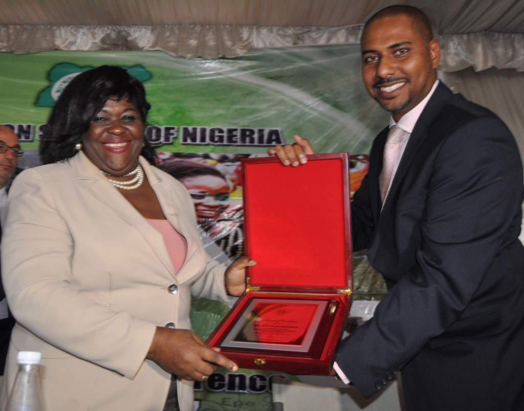 DG FIIRO Dr Mrs Gloria Elemo poses with Idris Nasreddin as they both display NSN Award of Excellence to NASCO Group CEO
