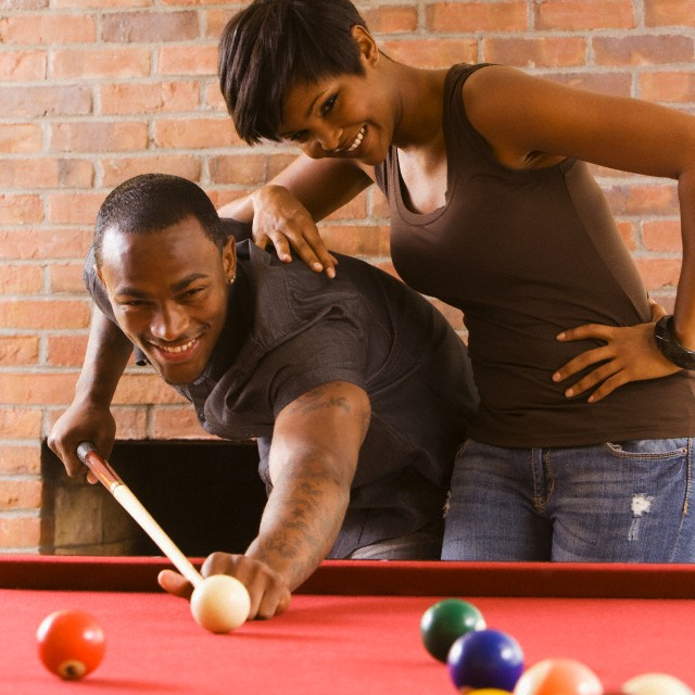 Atlanta, Georgia, USA --- African American couple playing pool --- Image by © Picturenet/Blend Images/Corbis