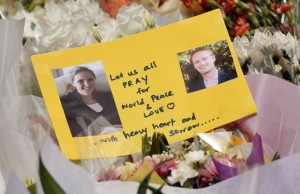 Photos of Katrina Dawson (L) and Tori Johnson, the two hostages killed during a fatal siege in the heart of Sydney's financial district, sit amongst flowers at a makeshift memorial near the scene, on December 17, 2014 (AFP) photo: William West