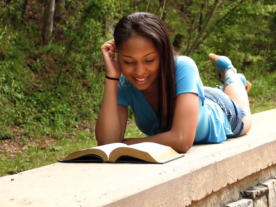 tmp_5105-5052-a-beautiful-african-american-teen-girl-reading-a-book-on-a-stone-wall-in-pv1841362193