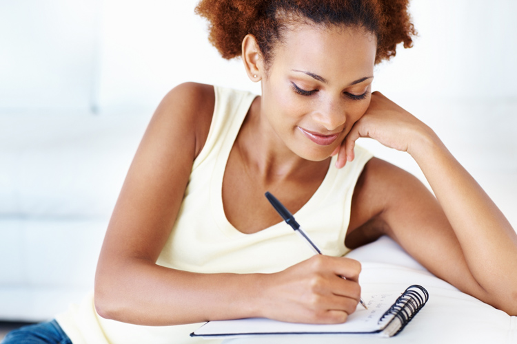 Closeup of smiling African American woman writing on notepad at home
